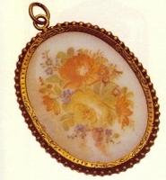 Medallón de opalina con flores, borde decorado y cerco de plata.