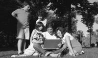 Maestro y alumnos en el parque con un portátil.